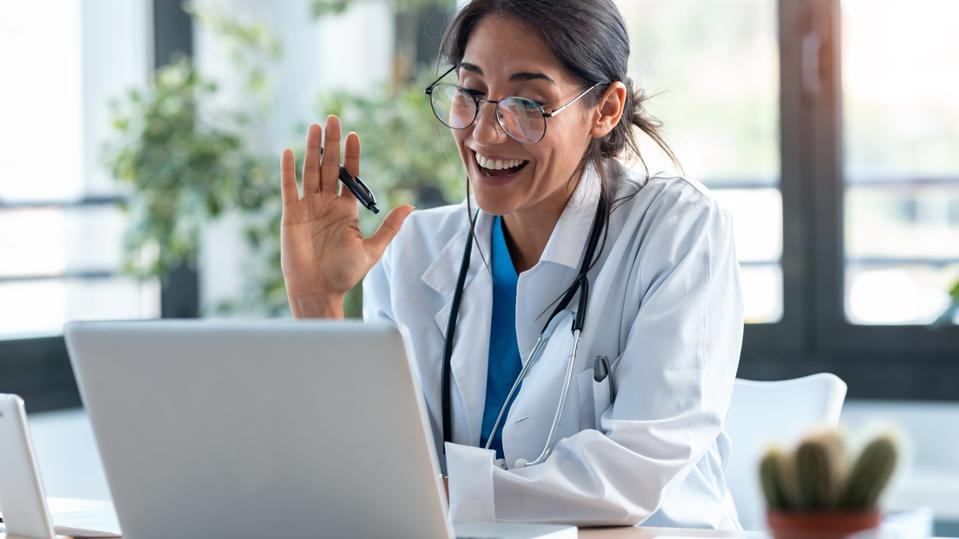 Female doctor waving and talking with colleagues through a video call with a laptop in the consultation.