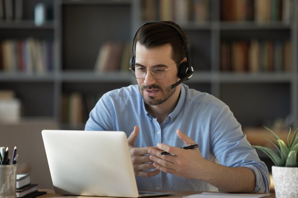 Confident man teacher wearing headset speaking, holding online lesson