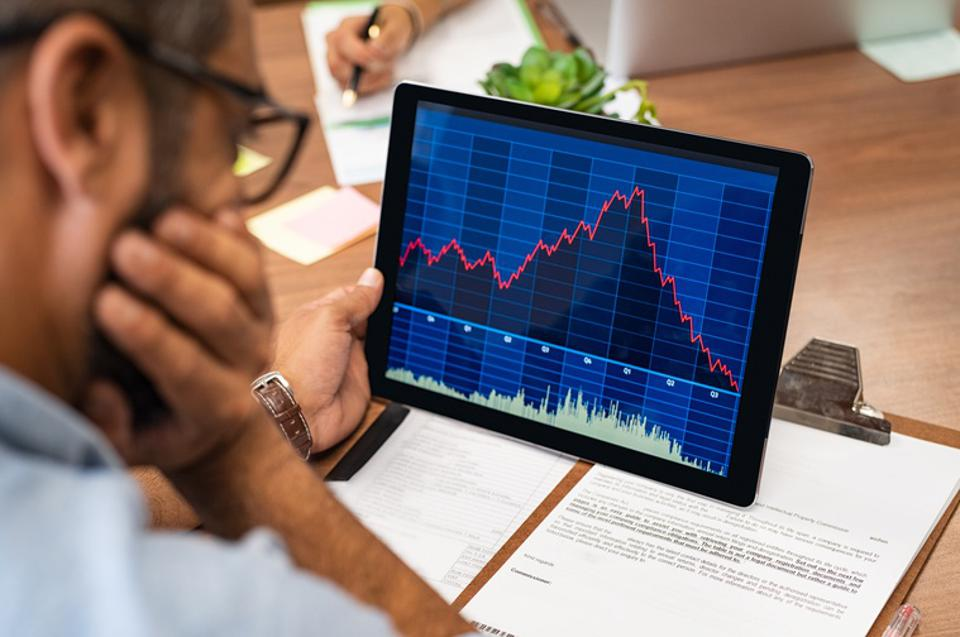 Man looking at stock market data on tablet