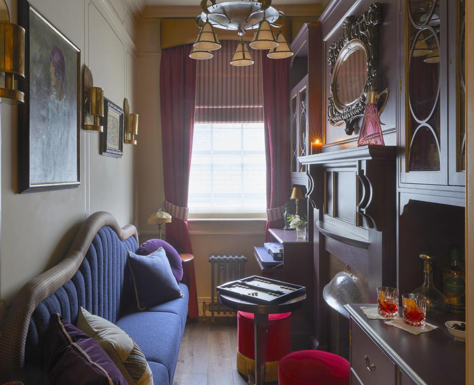 A small, narrow room with deep blue settee,  red velvet hassocks, dark wood paneling and cocktail bar