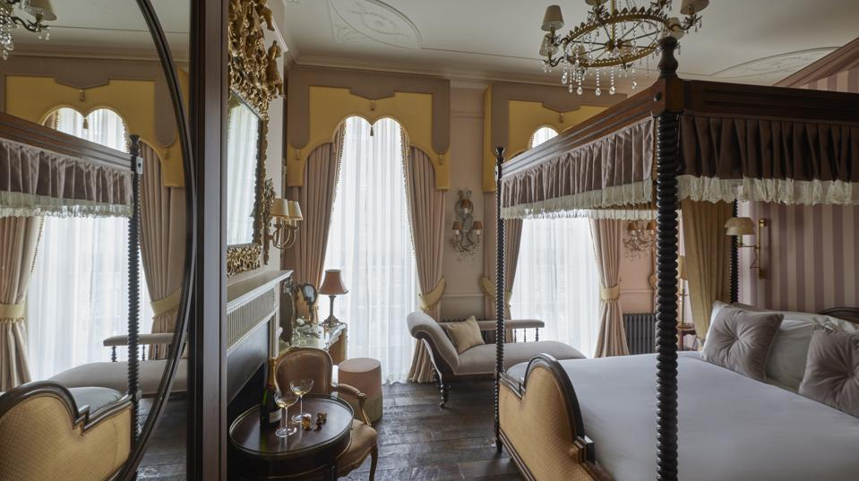 a golden toned bedroom with fourposter bed, crystal chandelier and gold framed mirror