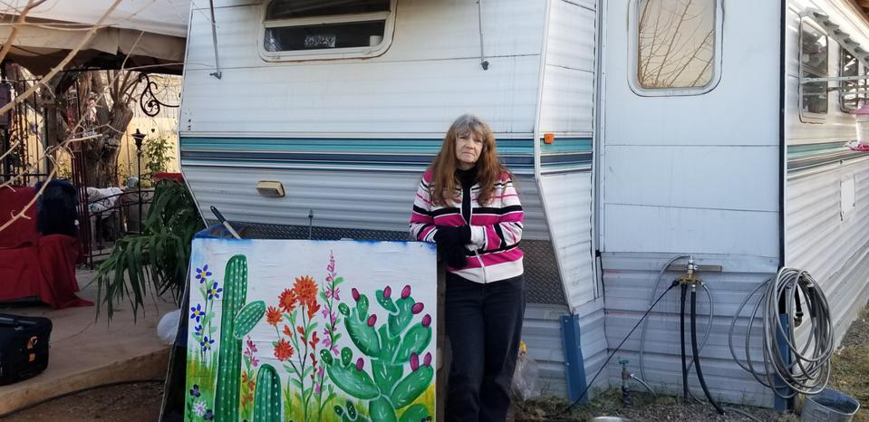 woman stands in front of trailer home