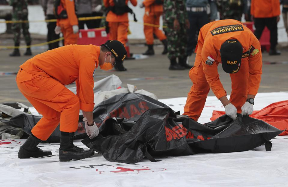 Rescuers carry a body bag containing human remains recovered when a Boeing 737 aircraft caring 62 people nosedived into the Java Sea in Indonesia in January, 2021