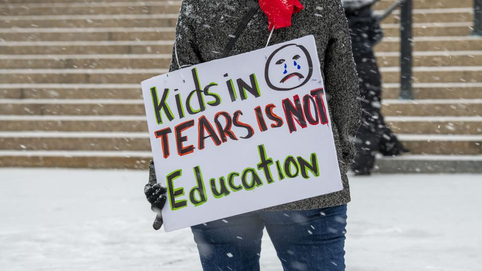 People rally to reopen the schools and put students back in the classroom during the coronavirus pandemic on a snowy day.