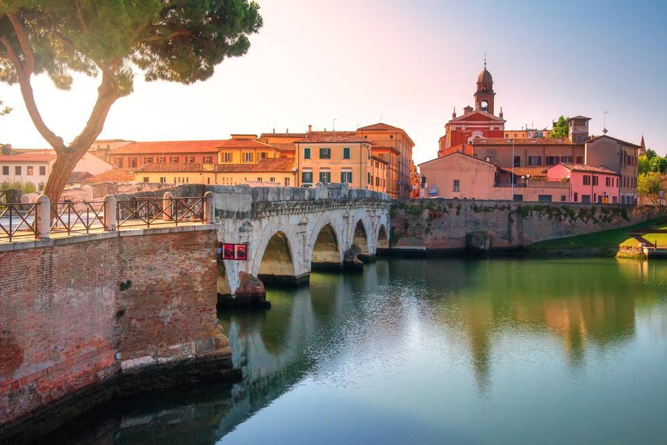Tiberius bridge in Rimini historic centre, Italy. Scenic ancient stone bridge in morning sunrise