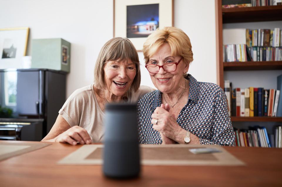 Excited senior friends using a smart speaker