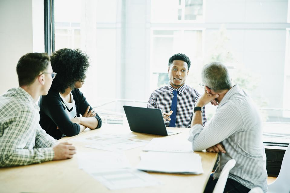 Businessman leading meeting with clients and colleagues in office conference room