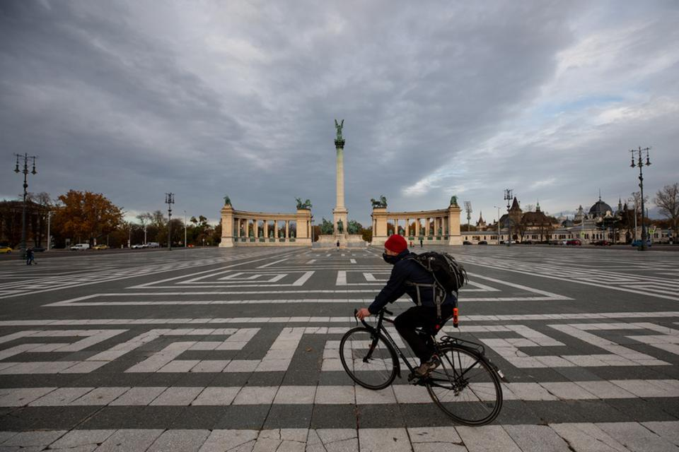 A cyclist crosses Heroes square in Budapest, Hungary.