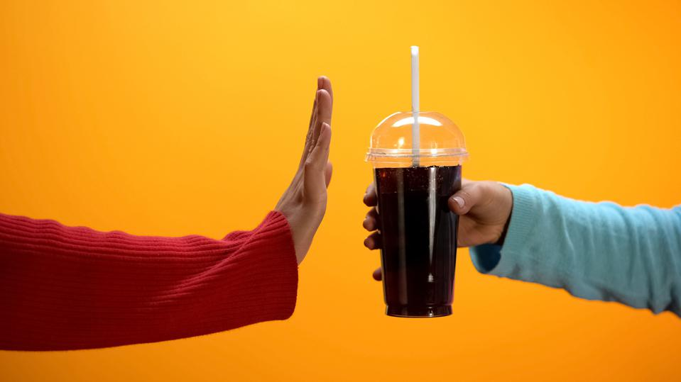 Lady showing stop gesture to soft drink on bright background, sugar overweight