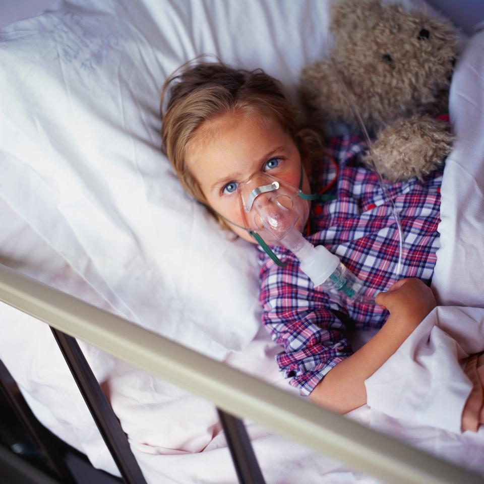 Child in hospital bed, wearing oxygen mask