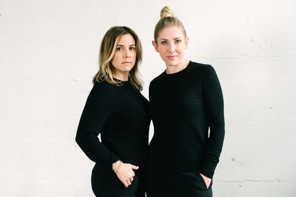 two women in black against a grey background