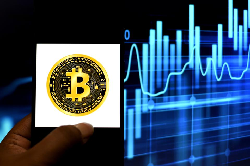 In this Photo illustration, the Bitcoin logo seen displayed...