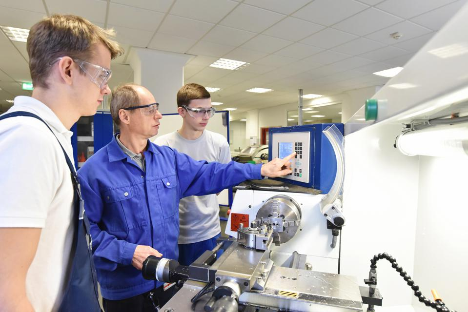 young apprentices in technical vocational training are taught by older trainers on a cnc lathes machine