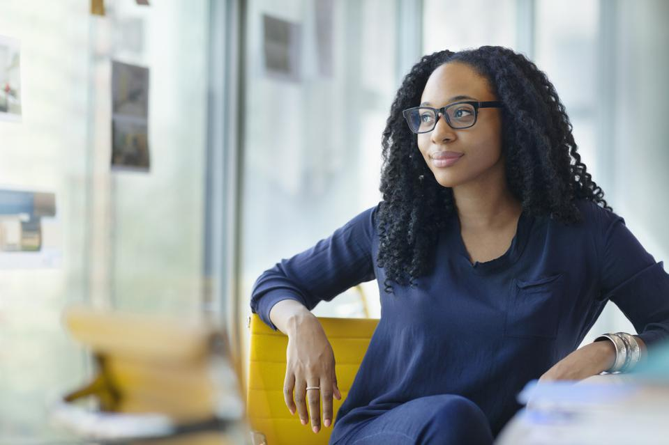 Portrait of woman sitting at desk in design office smiling
