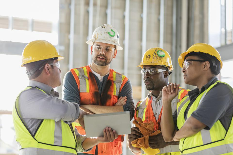 Construction workers looking at digital tablet