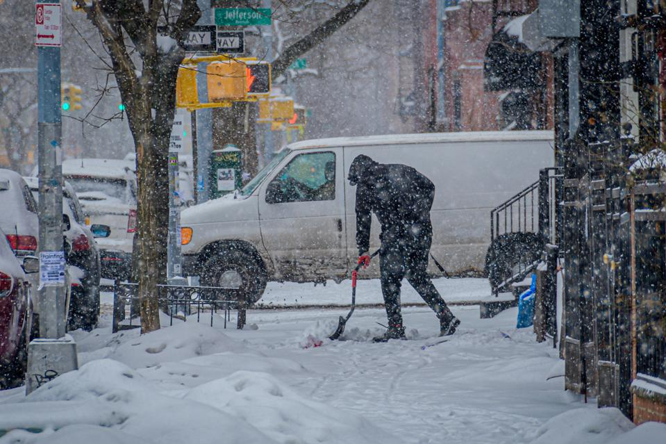 A man seen shoveling the snow covered streets. Millions of...