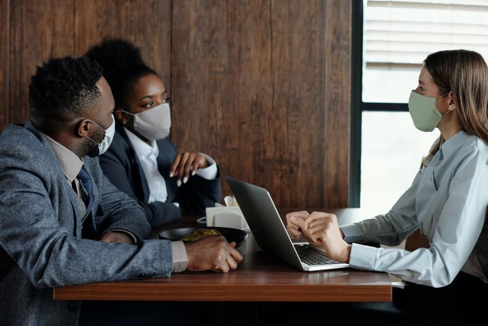 three people at a table wearing masks and discussing business