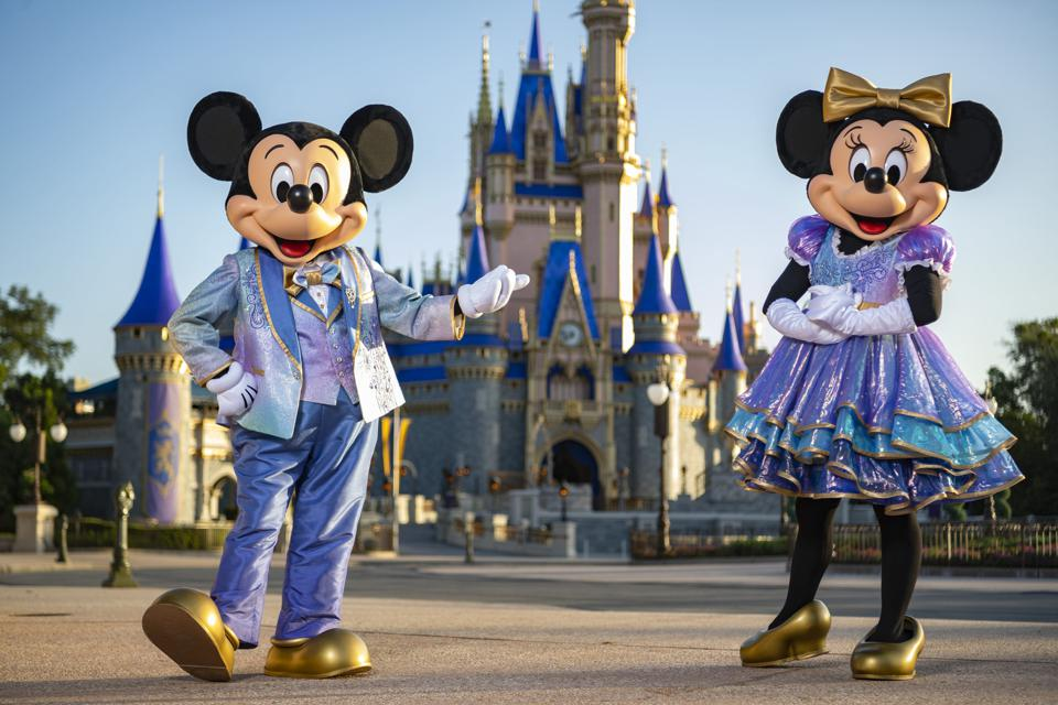 Mickey and Minnie Mouse standing in front of Cinderella Castle.