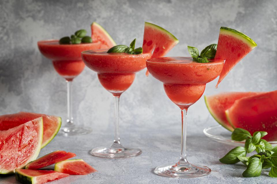 Frozen red drink margarita garnished with watermelon and basil.