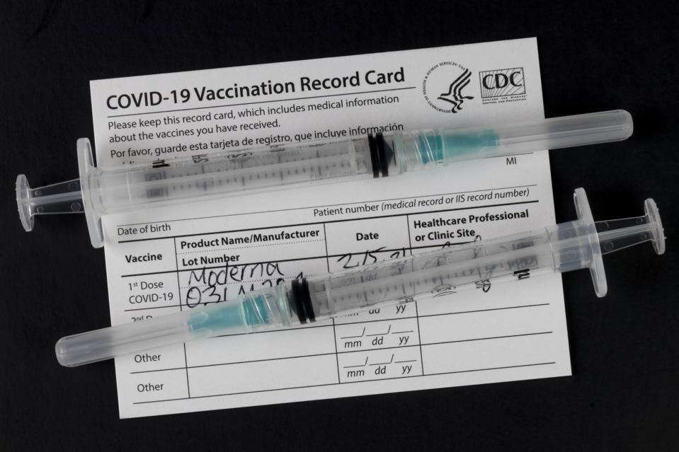 Indianapolis - Circa February 2021: COVID-19 Vaccination Record Card with syringes or hypodermic needles.