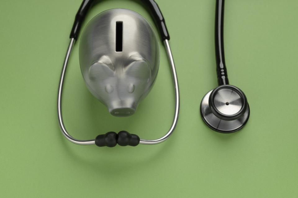 piggy bank with stethoscope on color background