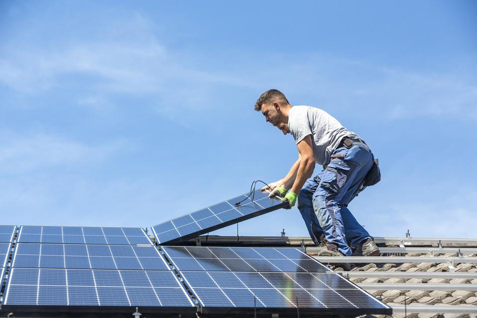 Men Holding Solar Panel While Standing On Roof Against Sky