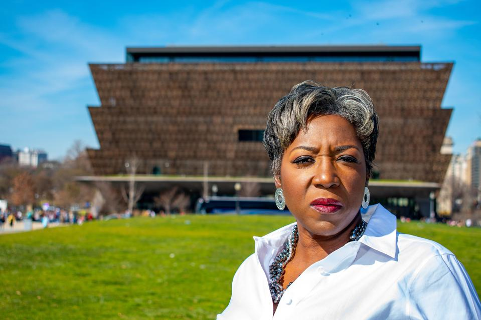 Cannabis activist Khadijah Tribble poses in front of Washing, D.C.'s African American Museum.