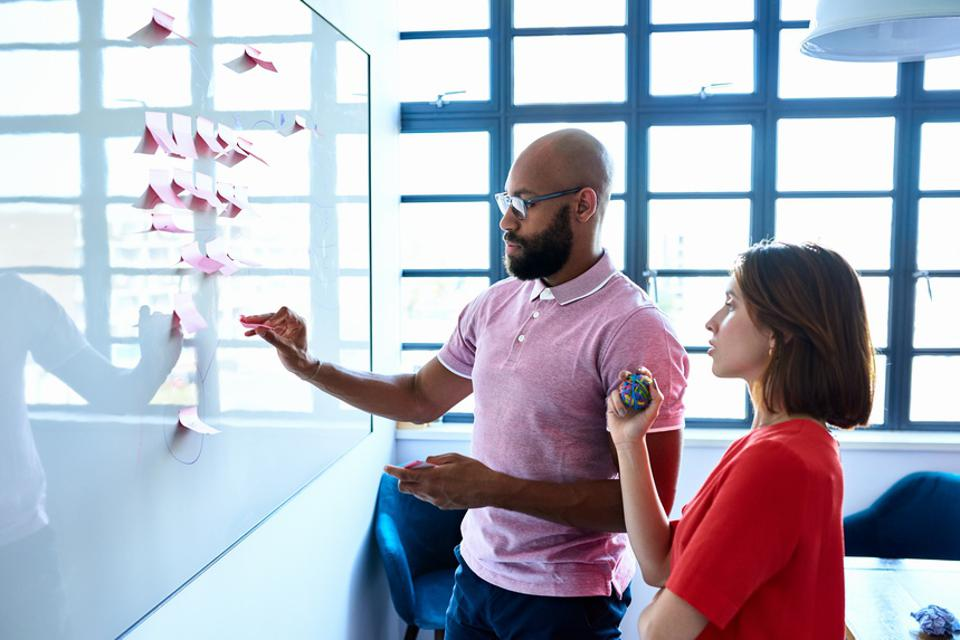 Young woman and male colleague writing ideas on adhesive notes