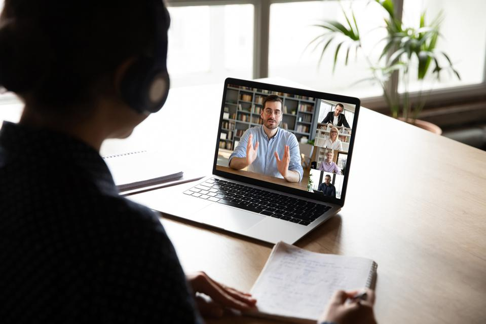 Pc screen view over woman shoulder during group videocall elearning