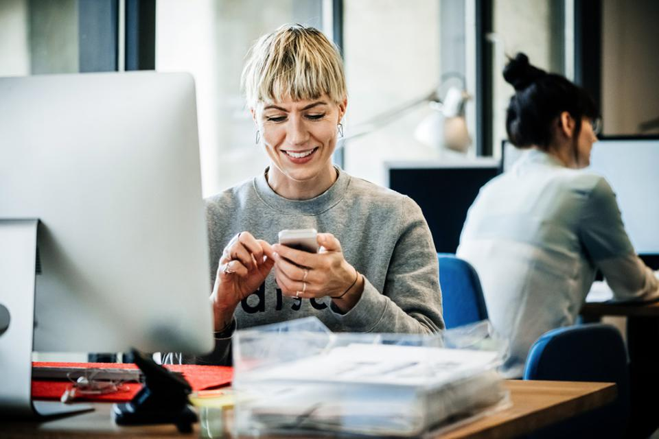 Start up business woman with smart phone sitting on desk