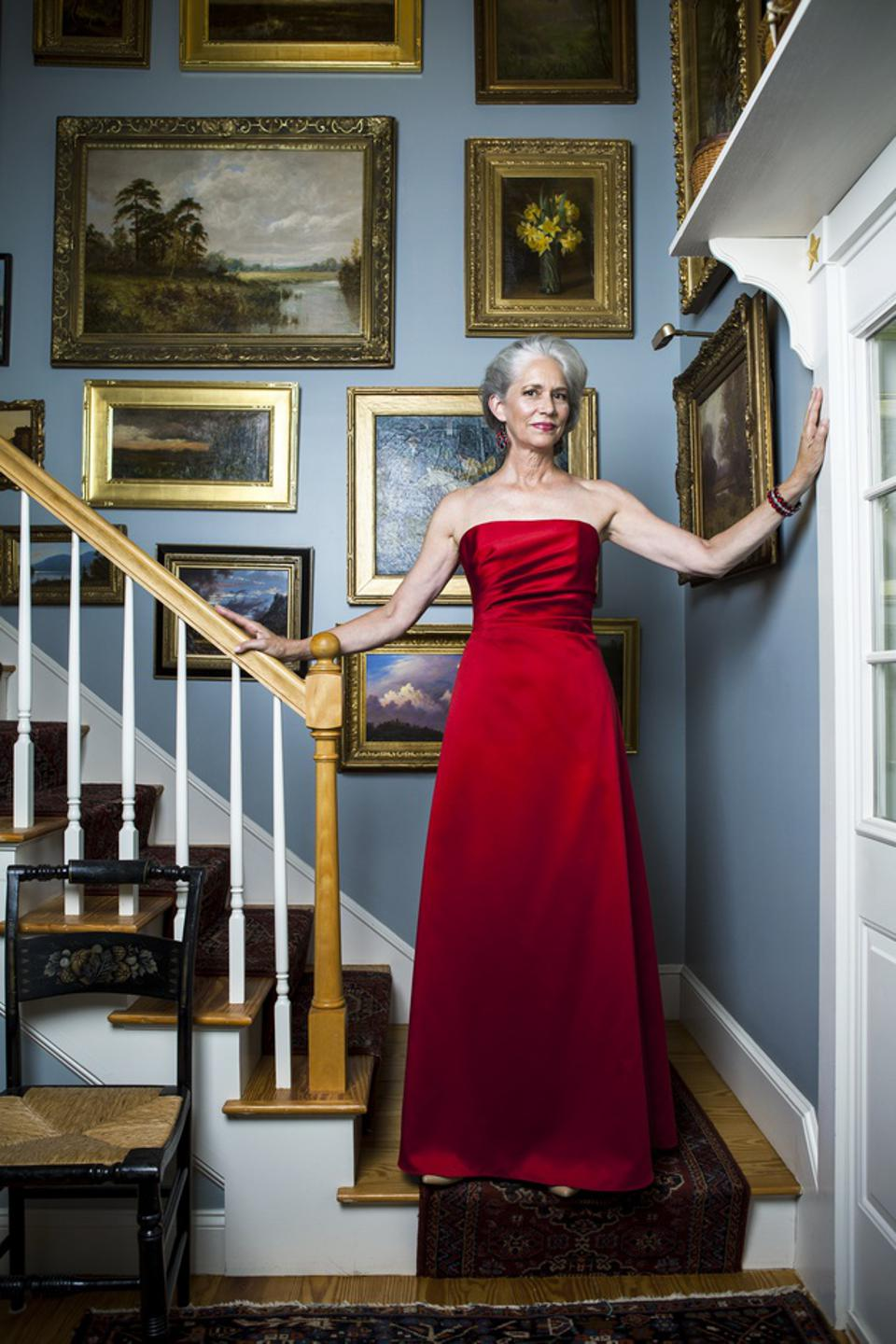 Beautiful woman in her late fifties with silvery gray hair wearing a glamorous red evening dress while standing in a staircase in front of gold-framed oil paintings.