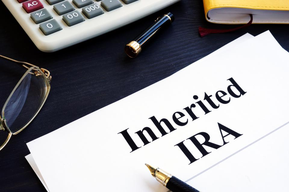 Documents on a table with ″Inherited IRA″ in black type. Calculator and glasses nearby.