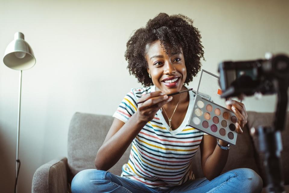 Beautiful African-American woman beauty vlogger recording makeup tutorial