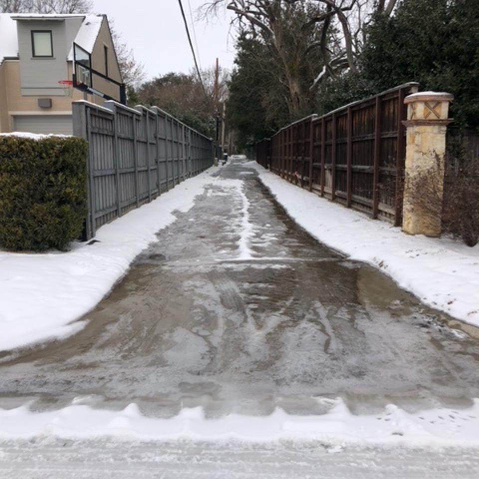 ice from a water pipe burst coats our alley