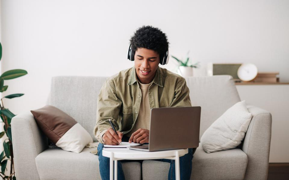 Conceito educacional baseado na web.  Estudante adolescente positivo em fones de ouvido, escrevendo no caderno durante a palestra on-line no laptop