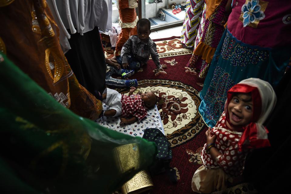 A baby lies on the floor of a prayer room as women pray on the day of Eid al-Adha celebrations at Haroon Mosque in Bangkok (LILLIAN SUWANRUMPHA/AFP/Getty Images)