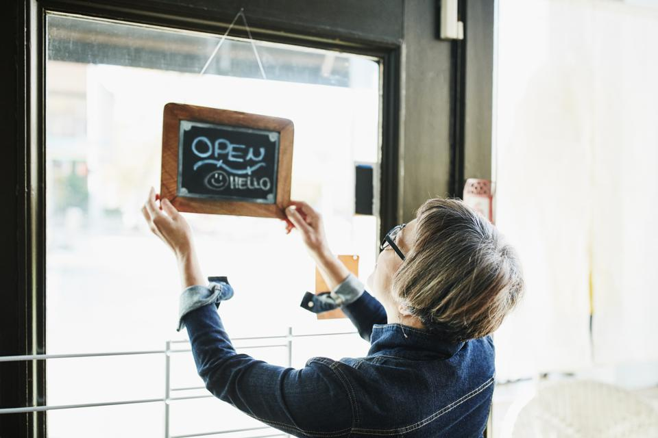 Senior female business owner turning open sign on door before opening boutique
