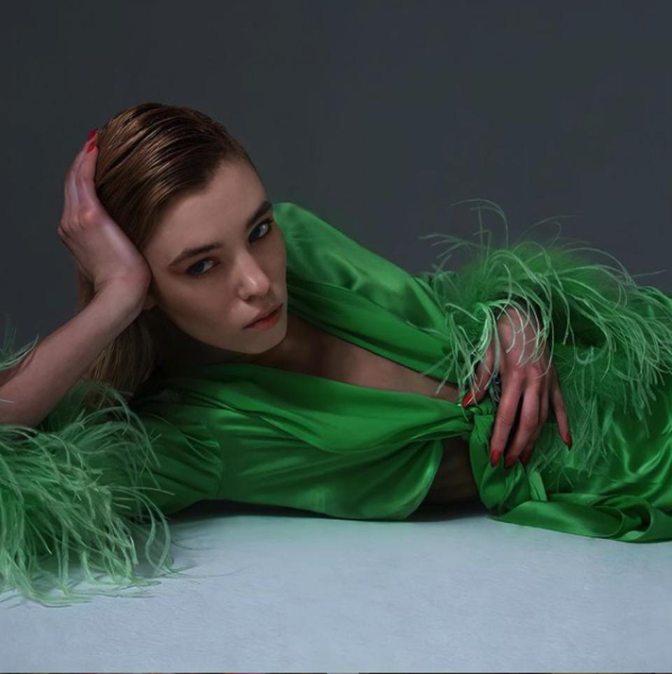 Model wearing knotted long sleeve silk shirt with feathers in green