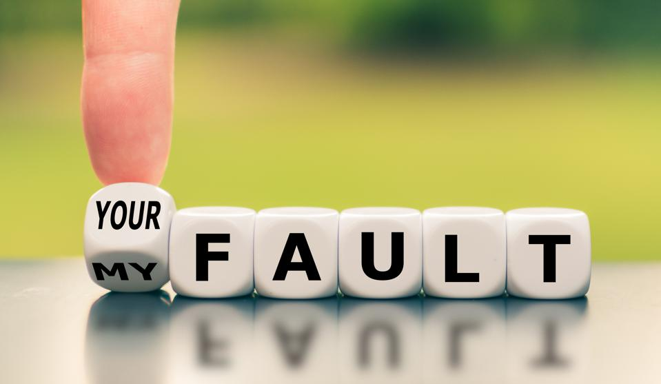 Hand turns a dice and changes the expression ″my fault″ to ″your fault″, or vice versa.