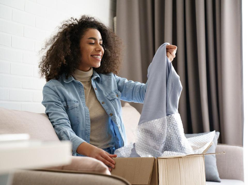 Young curly hair satisfied happy african girl woman lady shopaholic customer sit on sofa unpack parcel delivery box look at clothes take out grey pullover sweater, online shopping shipment concept.