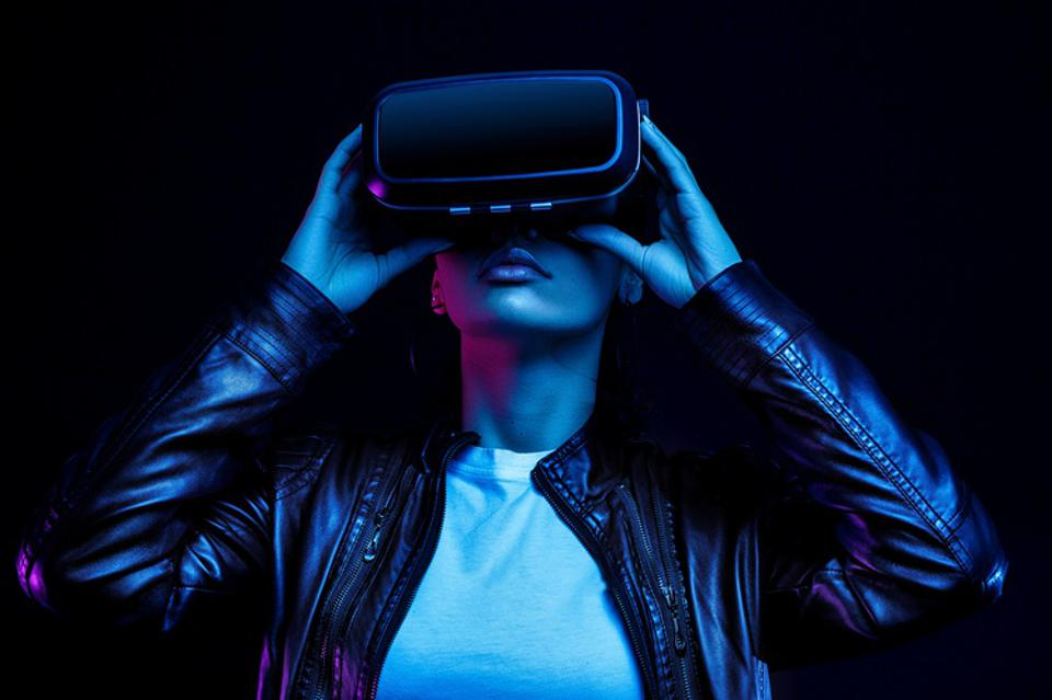 African american girl in vr glasses, watching 360 degree video with virtual reality headset isolated on black background, illuminated by neon lights