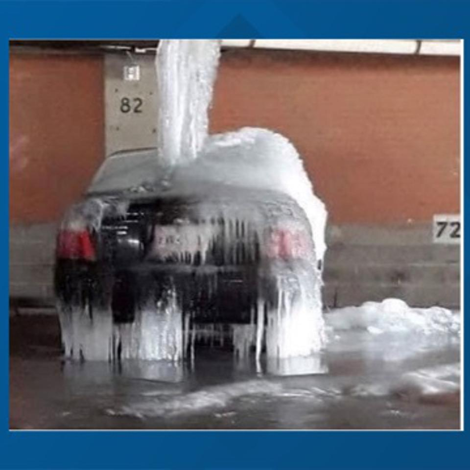Burst water pipes from the Texas winter storm freeze cover a downtown car in ice