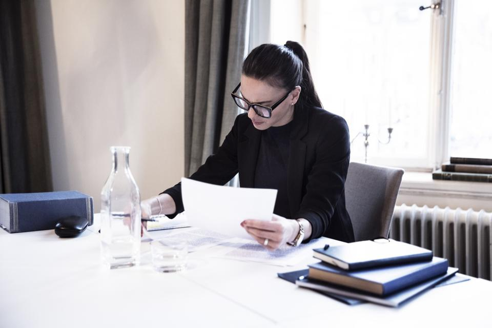 Female lawyer analyzing documents while sitting by desk in office