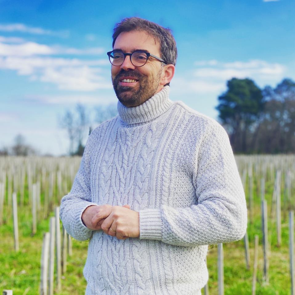 Loic Pasquet stands in a vineyard