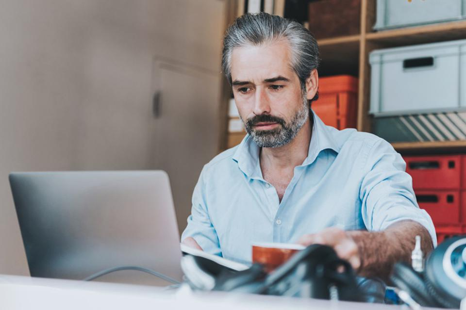 grey haired bearded man working at laptop in homeoffice
