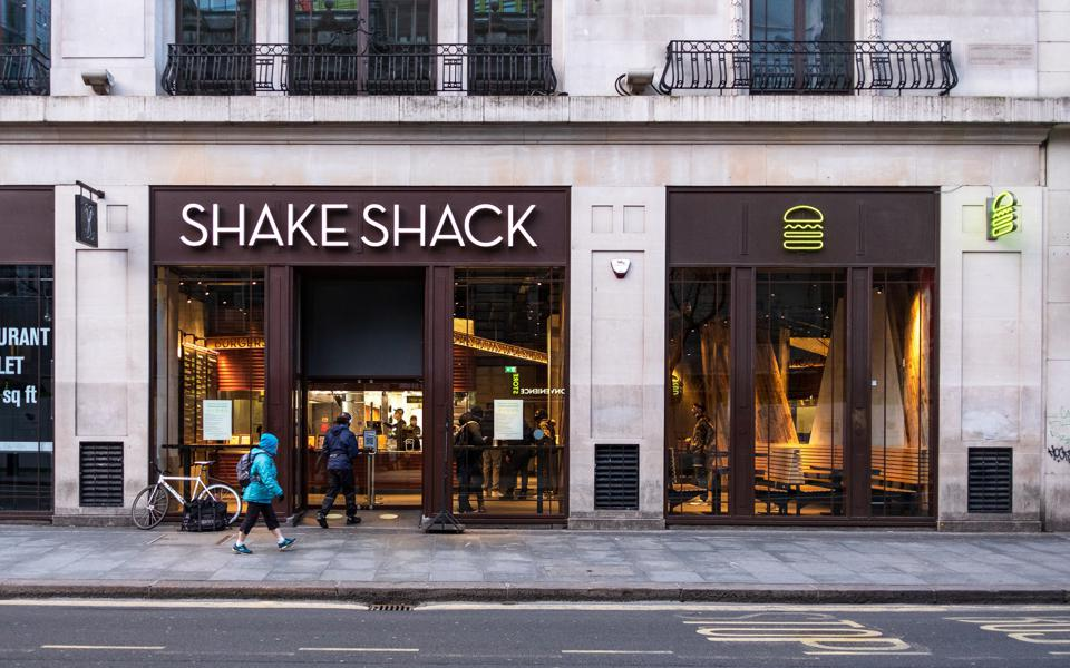 People queuing outside Shake Shack in London. Latest Covid-...