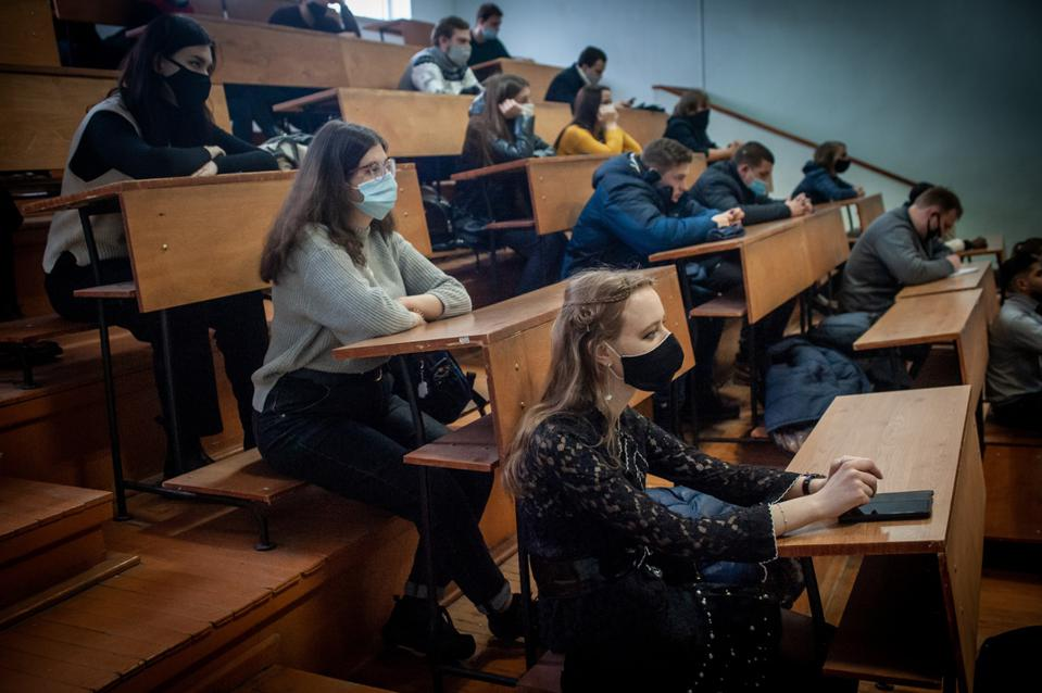 Students wearing face masks sit in a classroom at the Tambov...