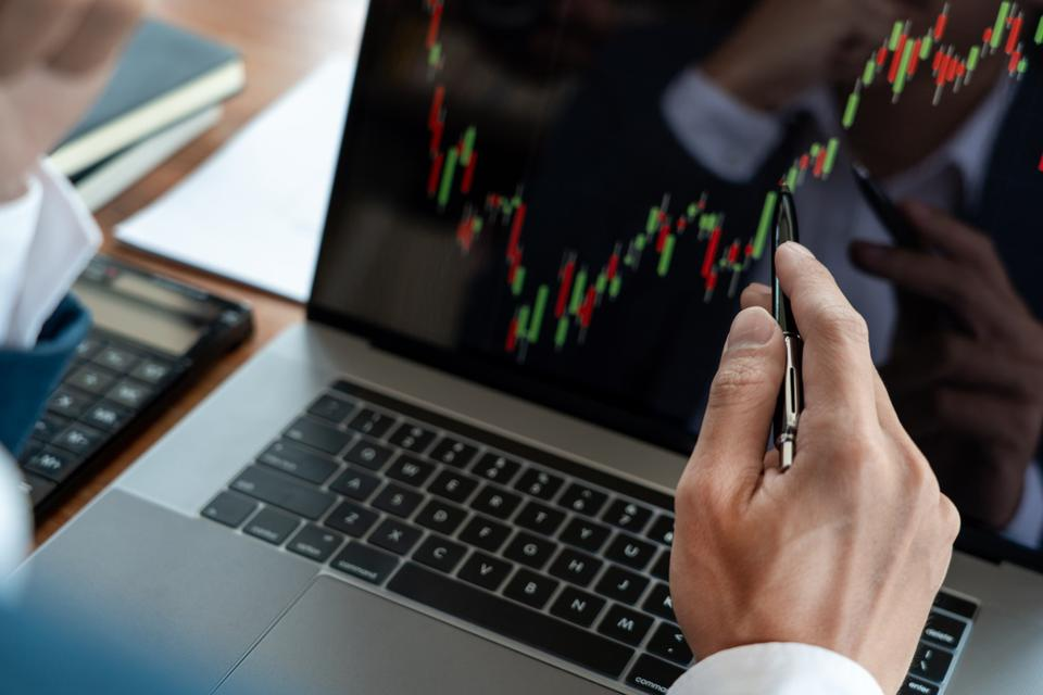 Businessman pointing at financial graph on laptop
