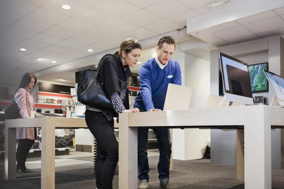 Salesman assisting female customer in buying laptop at store