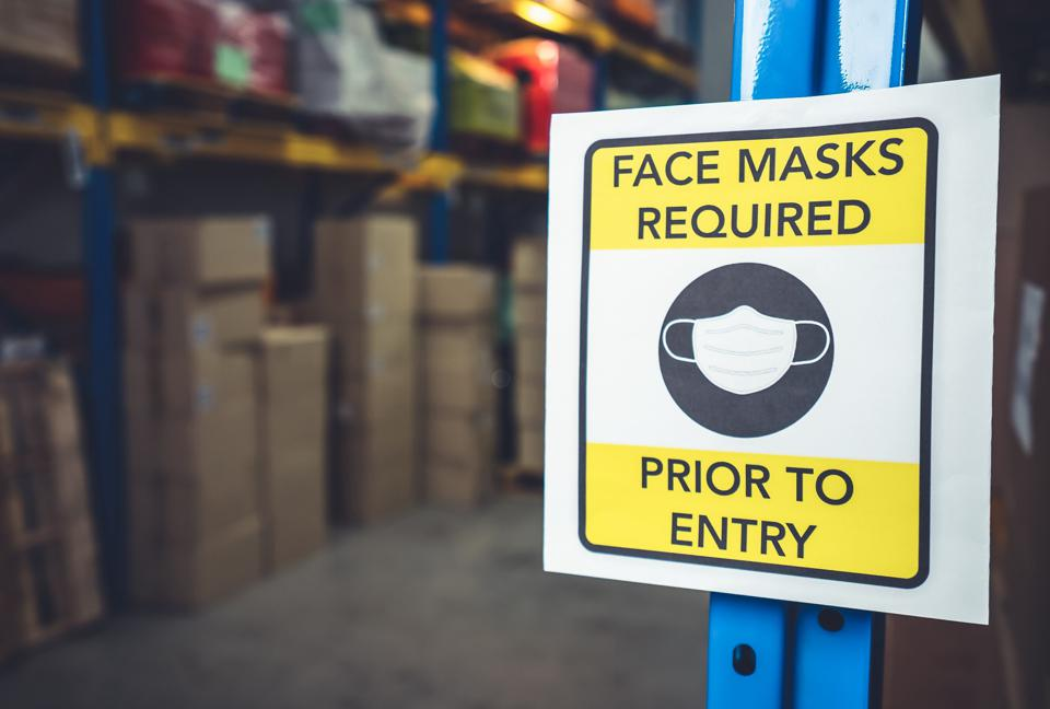 sign displayed in a warehouse directing that face masks are required prior to entry